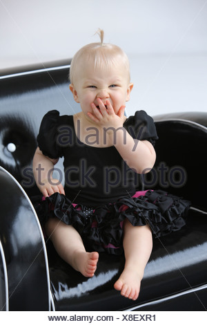 A Young Girl Yawning In A Chair; Gresham, Oregon, United States Of America - Stock Photo