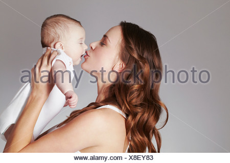 Mother kissing baby daughter - Stock Photo