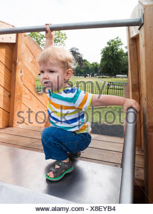Boy on playground slide - Stock Photo