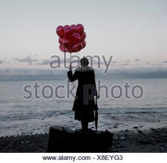 Woman holding bunch of red balloons standing large driftwood tree stump on beach - Stock Photo