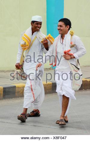 Two waris or pilgrims chatting on their route to Pandarpur - Stock Photo