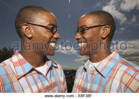 Outdoors portrait of twin African American teenage boys in glasses and matching plaid shirts - Stock Photo