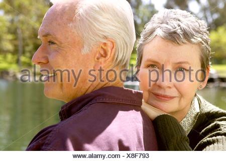Senior couple sitting by pond - Stock Photo