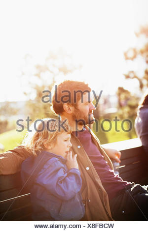 Sweden, Skane, Malmo, Vastra Hamnen, Father and son (6-7) sitting on park bench in sunlight - Stock Photo