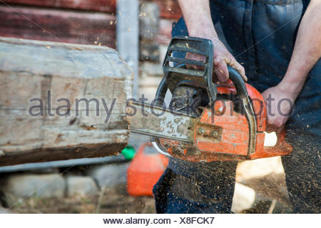 Finland, Close-up of man cutting log with chainsaw - Stock Photo