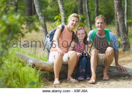 Portrait of a mature couple sitting on a tree trunk with their daughter in a forest - Stock Photo