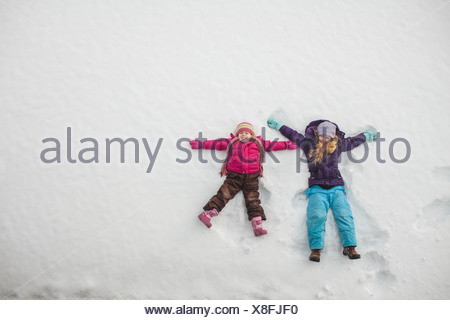 Two sisters playing, making snow angels in snow - Stock Photo