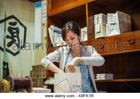 A small artisan producer of specialist treats, sweets called wagashi. A woman working packing sweet boxes for delivery. - Stock Photo