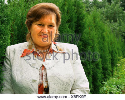Mature business woman smiling confidently - Stock Photo