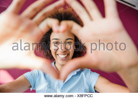 Portrait of young woman making heart shape with hands and fingers - Stock Photo