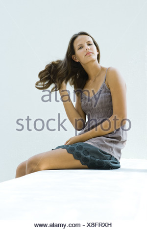 Teenage girl sitting, hand in hair, looking at camera - Stock Photo