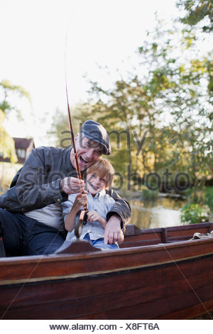 Grandfather and grandson fishing in boat - Stock Photo