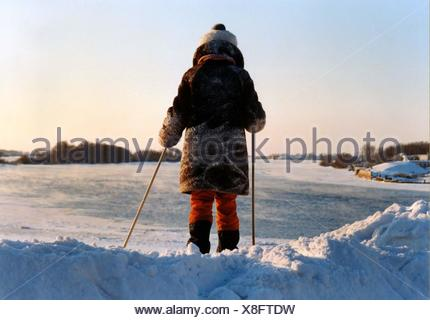 Rear View Of Girl Standing In Snow Holding Ski Poles - Stock Photo