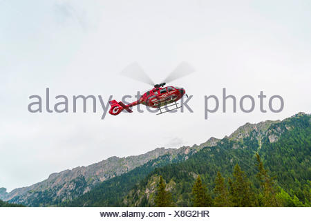 Red Aiut Alpin rescue helicopter I-AIUT taking off from meadow, Airbus Helicopter EC135T3, Funes Valley, Dolomites, Italy - Stock Photo