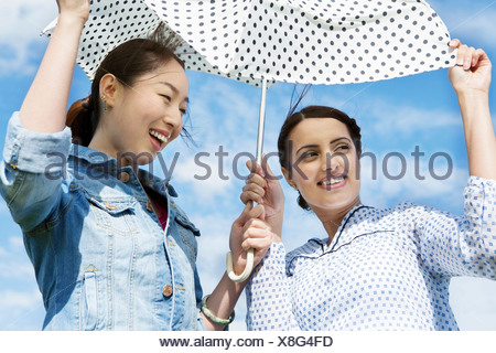 Two young women outdoors with parasol - Stock Photo