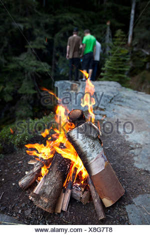 A campfire burns with three young men in the background looking over the edge of the cliff. - Stock Photo