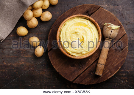 Wooden bowl with mashed potatoes and raw potatoes on dark background - Stock Photo