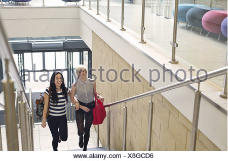 Young women walking up staircase