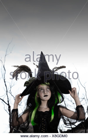 Girl costumed as witch looking up holding her hat - Stock Photo