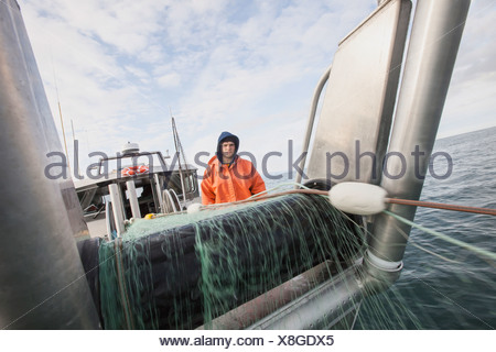 A Young Deckhand Watches And Waits For Fish As The Gillnet Is Pulled On Board. Salmon Fishing On The Copper River Flats - Stock Photo