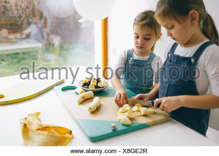 Two little girls chopping banana on the wooden board on the wooden board - Stock Photo