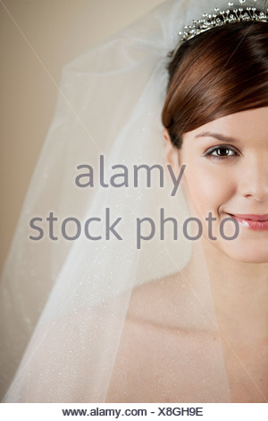 A young bride wearing a tiara and veil, left side of face - Stock Photo
