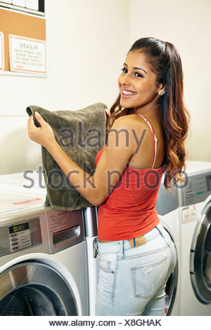 Young woman doing laundry in laundrette - Stock Photo