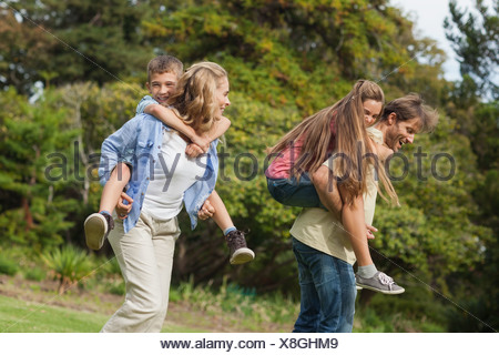 Parents carrying their children on their back - Stock Photo