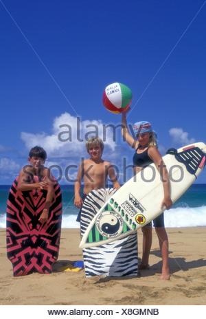 Kids with surfboards near ocean at Secret Beach, Kauai - Stock Photo
