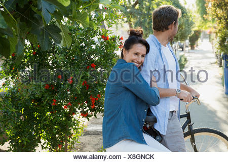 Portrait affectionate couple on bicycle - Stock Photo