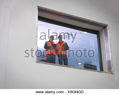 Engineers look out of window into hangar - Stock Photo