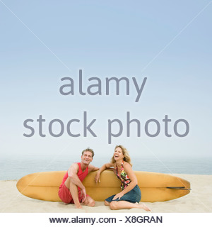 Mature couple sitting on the beach with a surfboard - Stock Photo