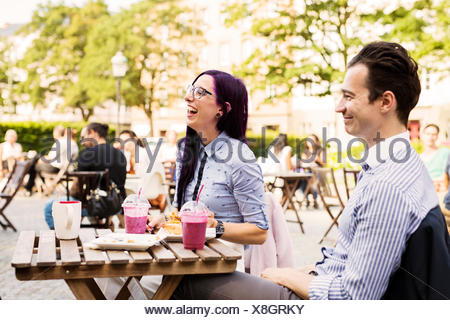 Friends having fun at outdoor cafe - Stock Photo
