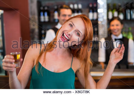 Portrait of drunk woman with tequila shot laughing in front of counter - Stock Photo