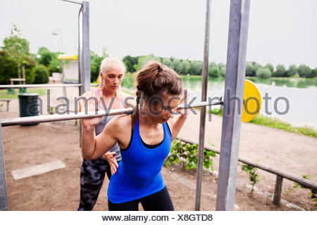 Young woman assisting friend in lifting barbell at park - Stock Photo
