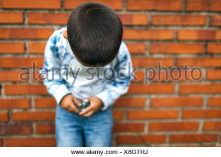 Head of little boy leaning on brick wall looking down - Stock Photo