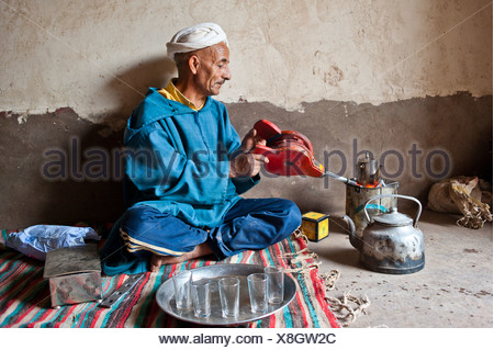 Elderly Berber man wearing a turban sitting on the floor on a rug preparing traditional mint tea, kindling the fire in a little - Stock Photo