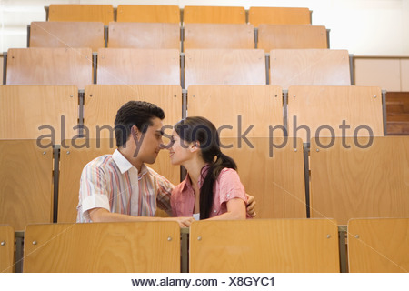 Students kissing in empty classroom - Stock Photo