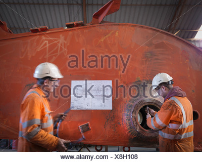 Engineers working on excavator parts in surface coal mine - Stock Photo