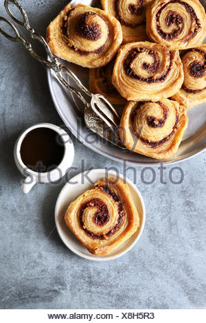 Puff pastry cinnamon rolls on tray with a cup of coffee.Top view - Stock Photo