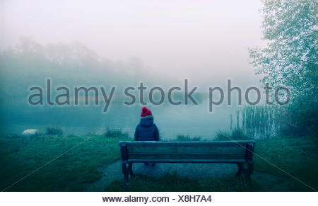 Canada, British Columbia, Greater Vancouver Regional District, Vancouver, Boy sitting on bench - Stock Photo
