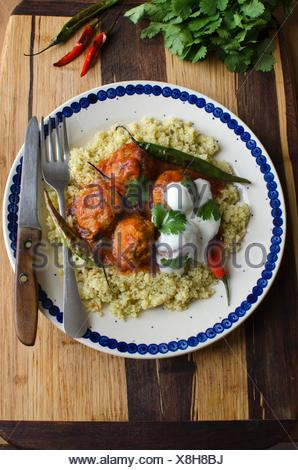 Meatballs in tomato sauce with couscous and chilli peppers. - Stock Photo