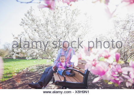 Grandfather and grandchild on park bench - Stock Photo