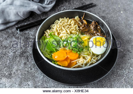 Bowl of ramen soup with spinach, carrot, boiled egg, bamboo sprouts and mushrooms - Stock Photo