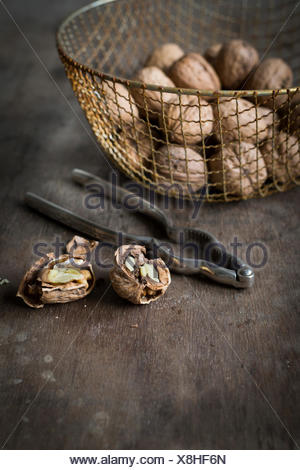 Walnuts in vintage wire basket on wooden table - Stock Photo