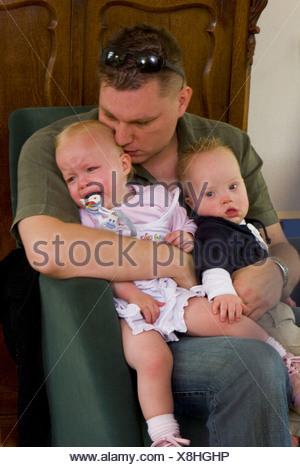 Father hugging twin babies, one has down syndrome - SerieCVS417399 - Stock Photo