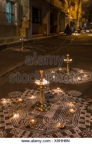 Traditional Rangoli, Kolam or Muggu, decorative pattern, and oil lamps in front of a house entrance, Tamil quarter, Kochi - Stock Photo