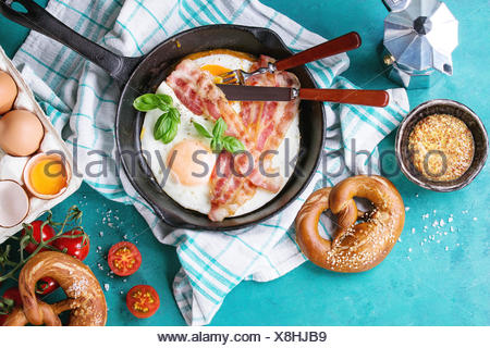 Breakfast with fried eggs and bacon in cast-iron pan, broken egg, tomatoes, mustard, pretzels and basil on white kitchen towel over turquoise wooden b - Stock Photo