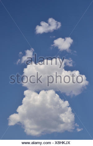 A vertical image of white puffy clouds on a clear blue Alberta sky. - Stock Photo