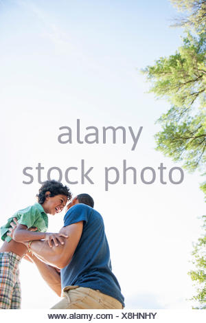 Father playing with his son, lifting the boy up in the air. - Stock Photo